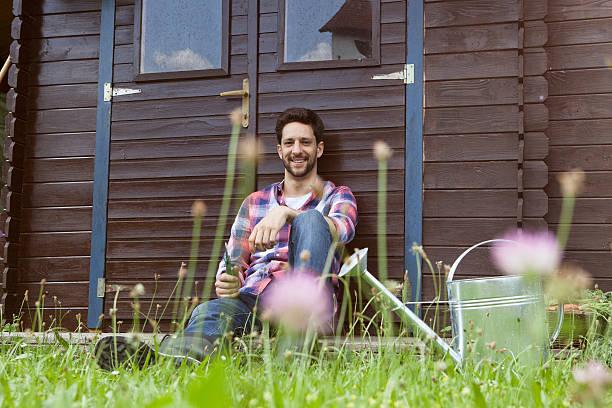 Homme souriant appuyé contre un abri de jardin en bois